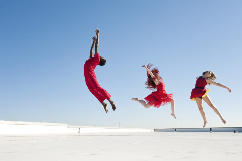 Three dancers leap into the air, looking skyward.