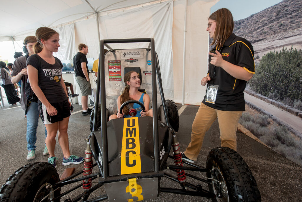 Festival-goer tries out UMBC Racing's Baja vehicle.