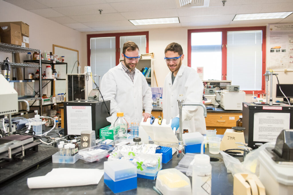 A profess and student do an experiment in a lab, wearing protective gear