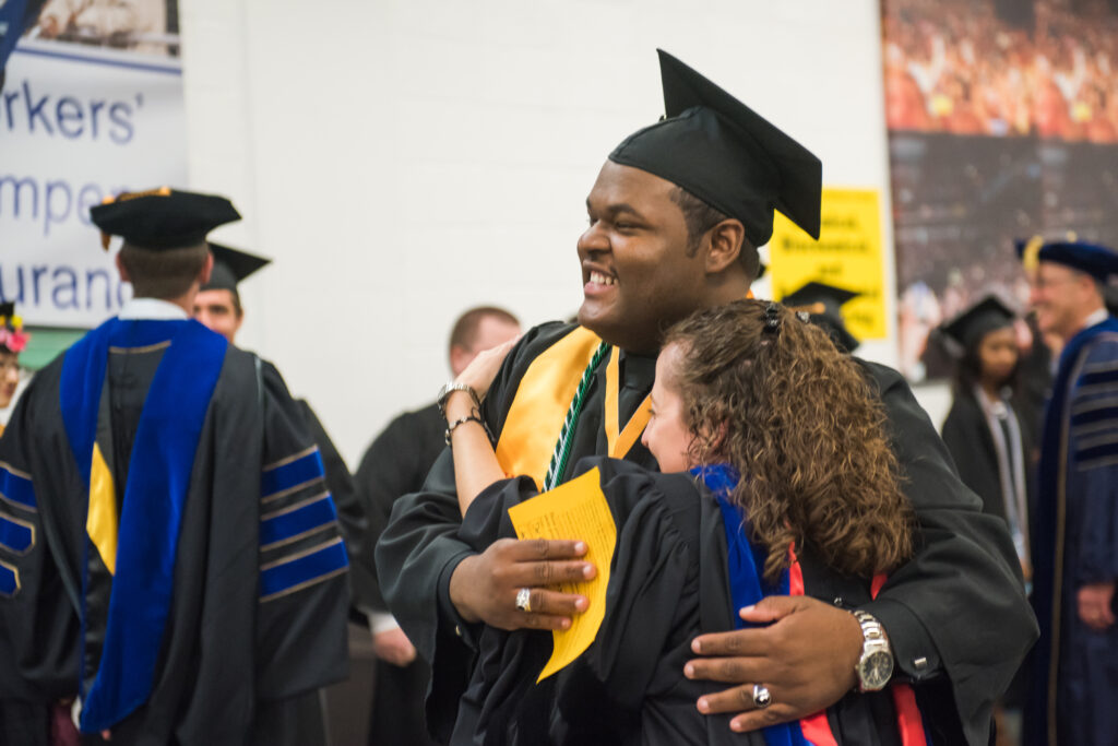 A faculty mentor congratulates Da'Kuawn Johnson, highlighted in UMBC's Class of 2017.