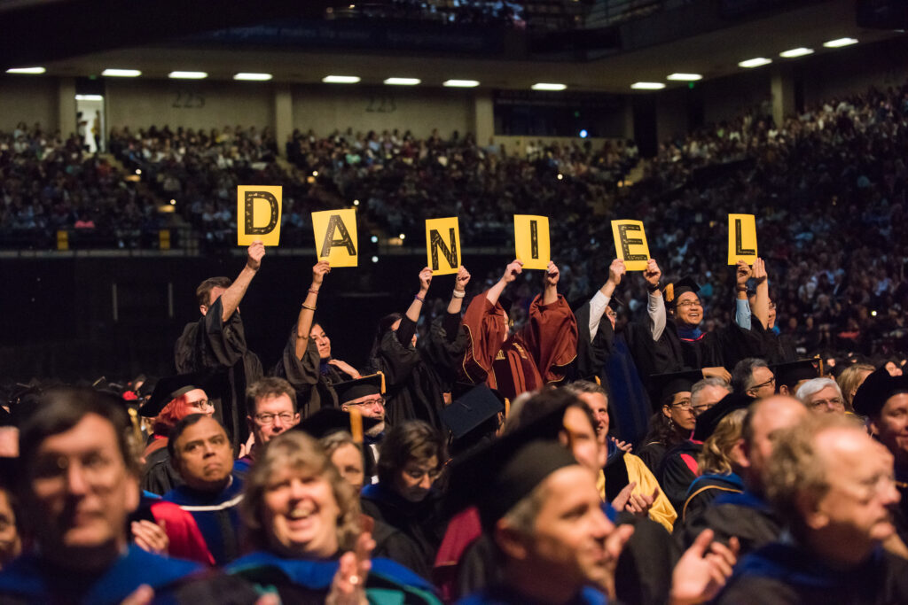Professors hold signs spelling out D-A-N-I-E-L