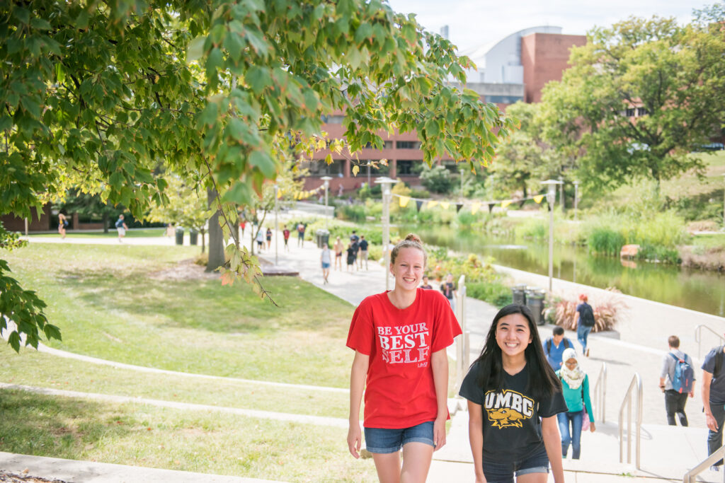 Two students walk near the library pond, one in a red shirt and one in a black shirt with UMBC athletics logo.