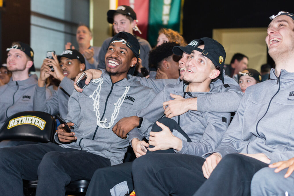 Basketball players in matching gray jackets and black hats celebrate, hugging each other.