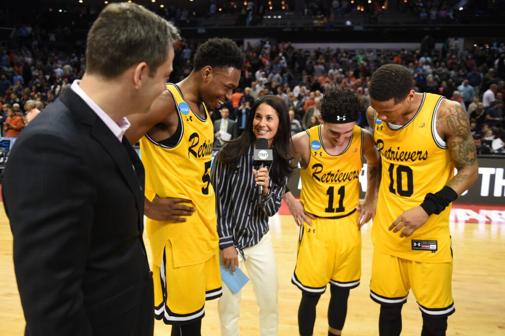 Journalist (center) holds microphone and speaks with coach and three players in yellow jerseys.