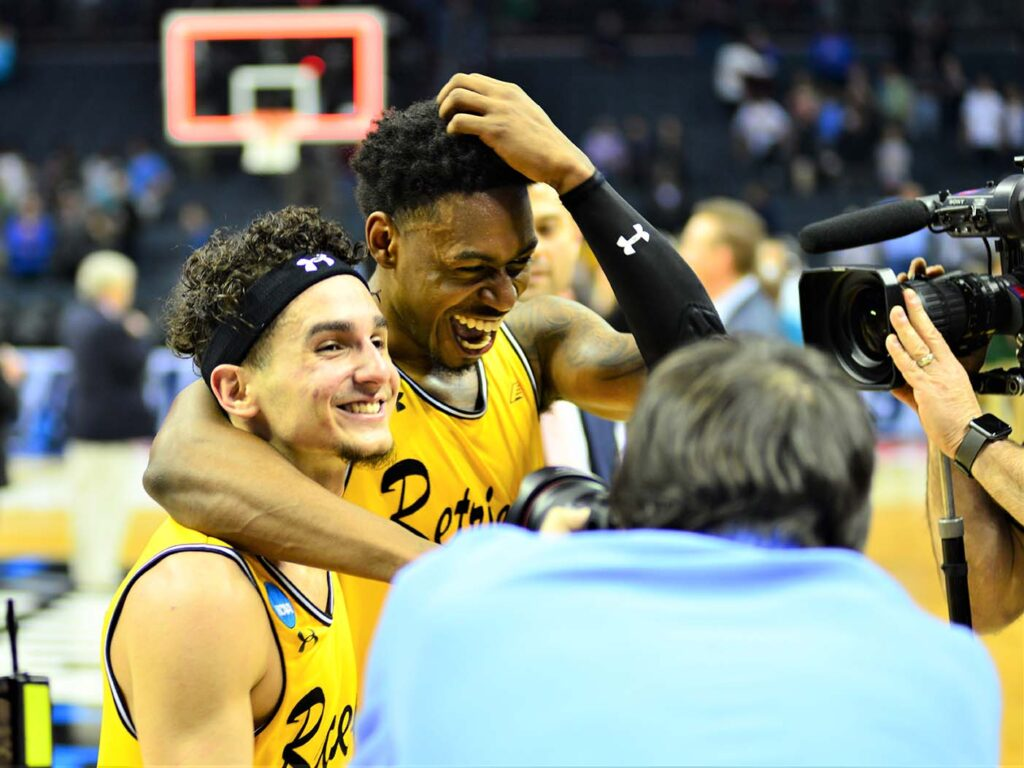 Two basketball players in gold jerseys smile and embrace.