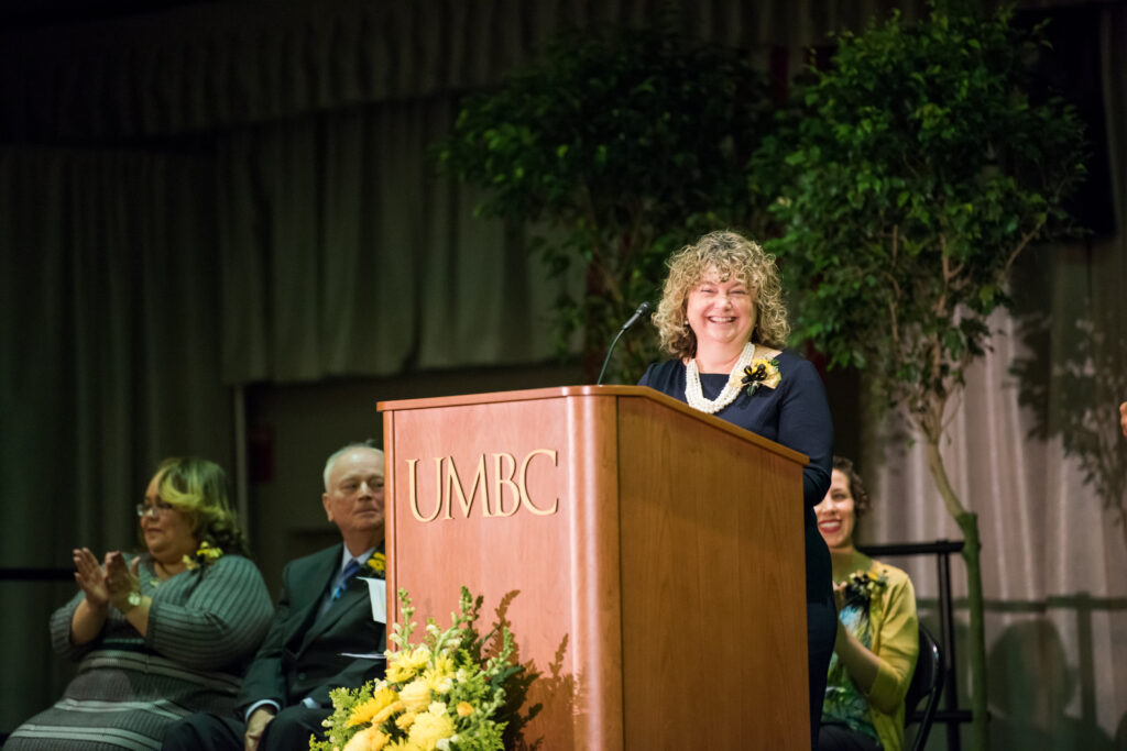 Professor in blue dress and beaded necklace stands at podium, smiling.