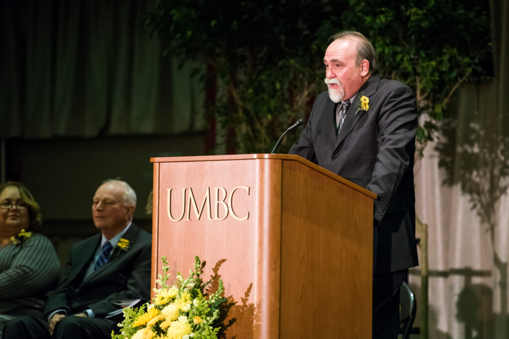 Man in suit, with gray beard, speaks at podium