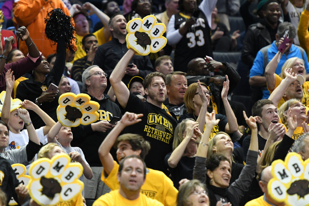 Fans cheering, holding and wearing UMBC fan gear.
