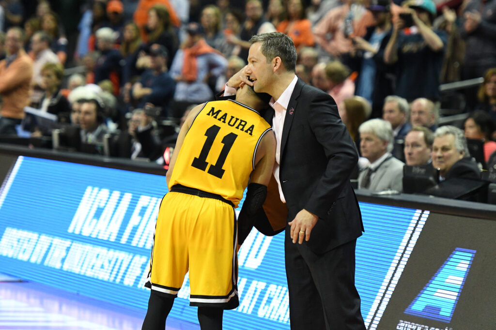 Coach hugs basketball player in yellow jersey.