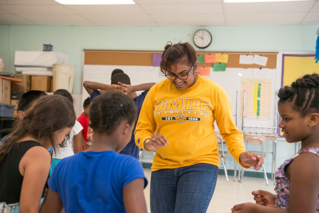 College student in yellow UMBC shirt leads elementary students in a movement-based activity.