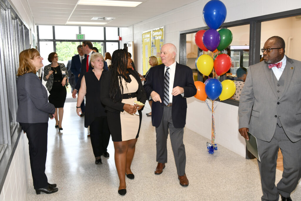 Group takes a tour of a newly renovated building, with balloons decorating the space.