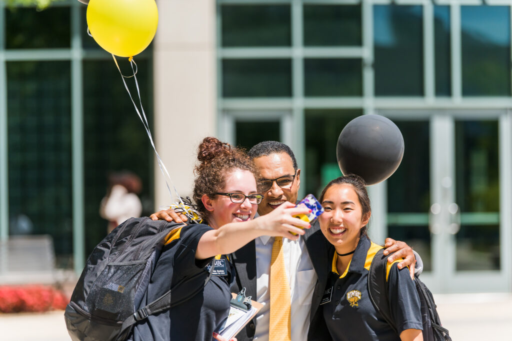 University president in suit poses for a selfie with two student leaders in black t-shirts with UMBC logo.
