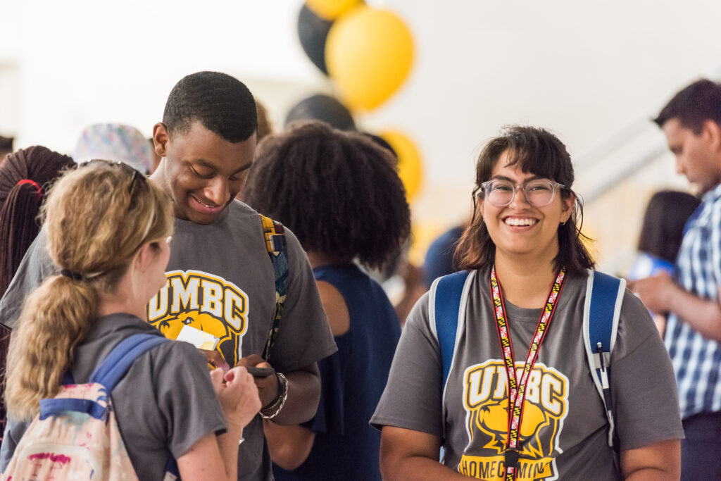 Three students wearing UMBC shirts cluster in a group, with one looking up toward the camera.