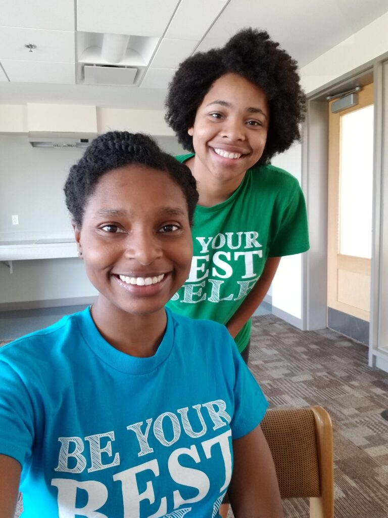 "Two young women smile in a selfie, wearing ""Be Your Best Self"" t-shirts."