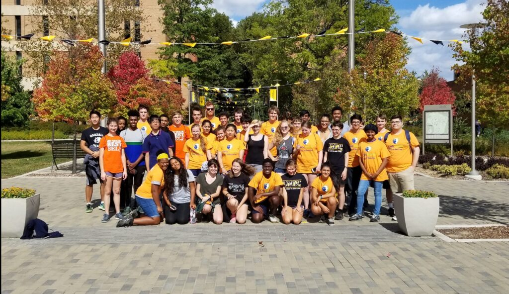 A group of UMBC students in gold t-shirts poses in front of campus.