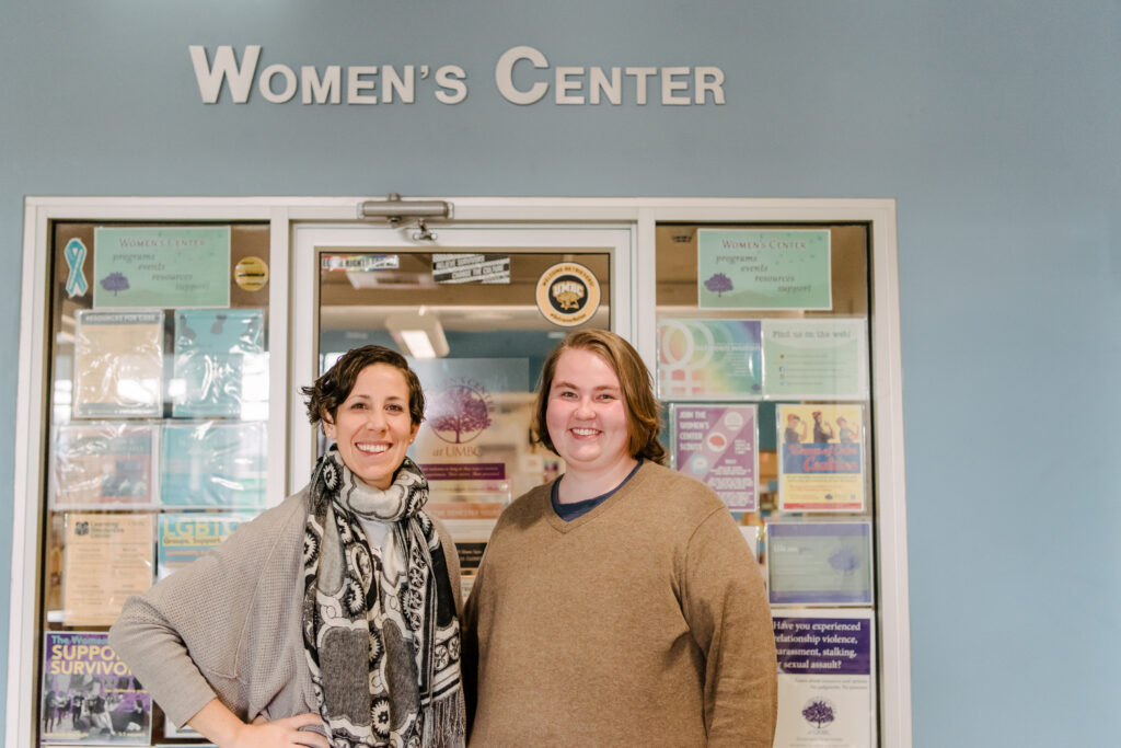 Two people -- one in gray sweater and patterned scarf and one in light brown sweater -- pose in front of the UMBC Womens Center.