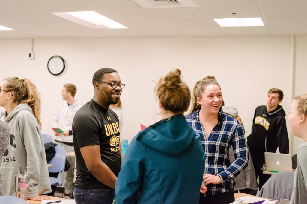 Small group of college students chats in a classroom.