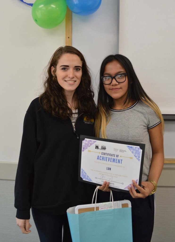 Two young women pose for a portrait, one holding a gift back and achievement certificate.