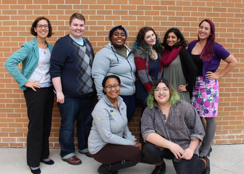 Eight people in their 20s and 30s, of diverse identities, stand in two rows in front of a brick wall.