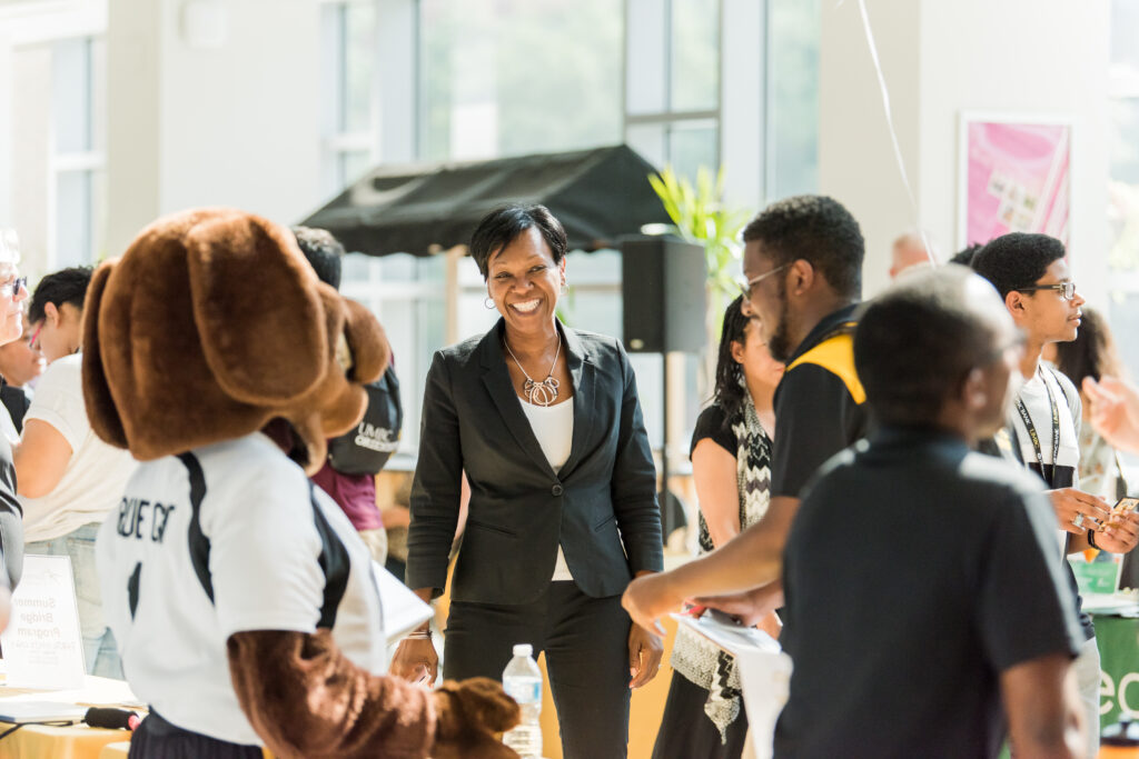 Yette Mozie-Ross with UMBC mascot True Grit and students in 2019