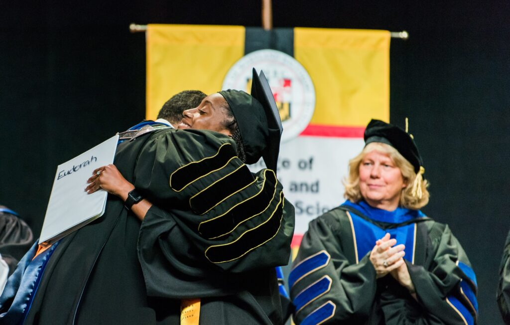 University president hugs undergraduate commencement speaker in congratulations following her remarks, while colleagues clap, all in graduation attire.