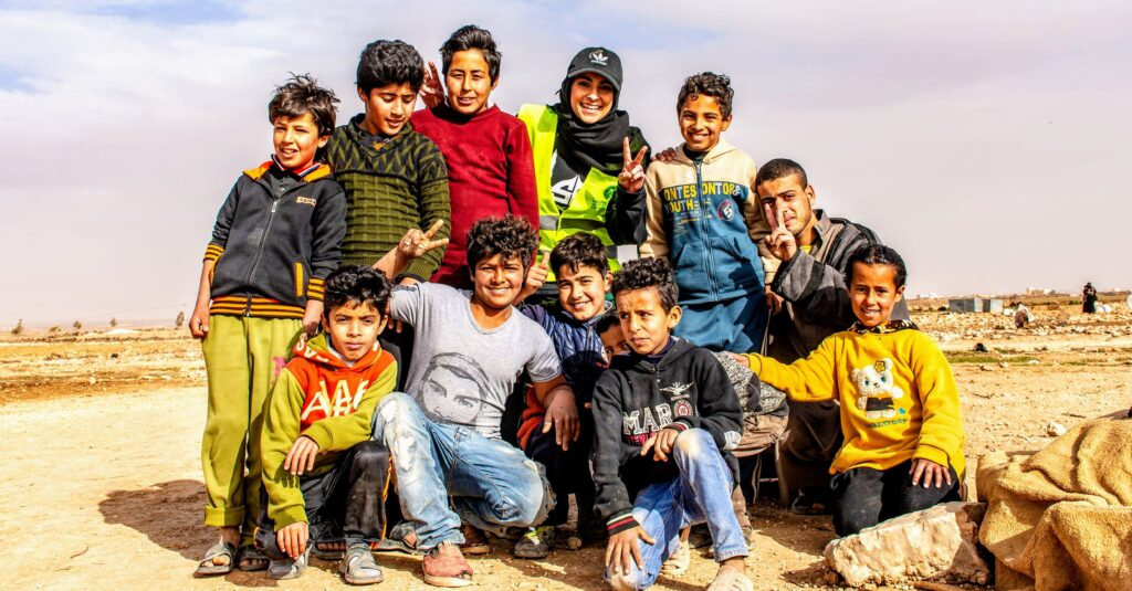 Maheen posing with boys from Syrian refugee camp after handing out soccer jerseys she helped to fundraise.