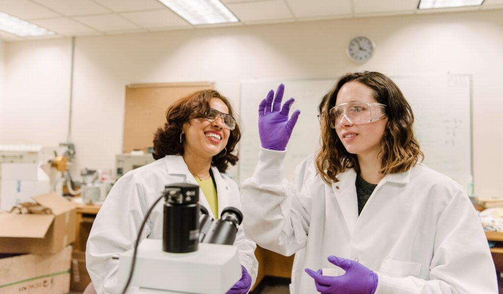Two women work in a lab, with the student looking at a slide while her professor looks on; they wear gloves and goggles