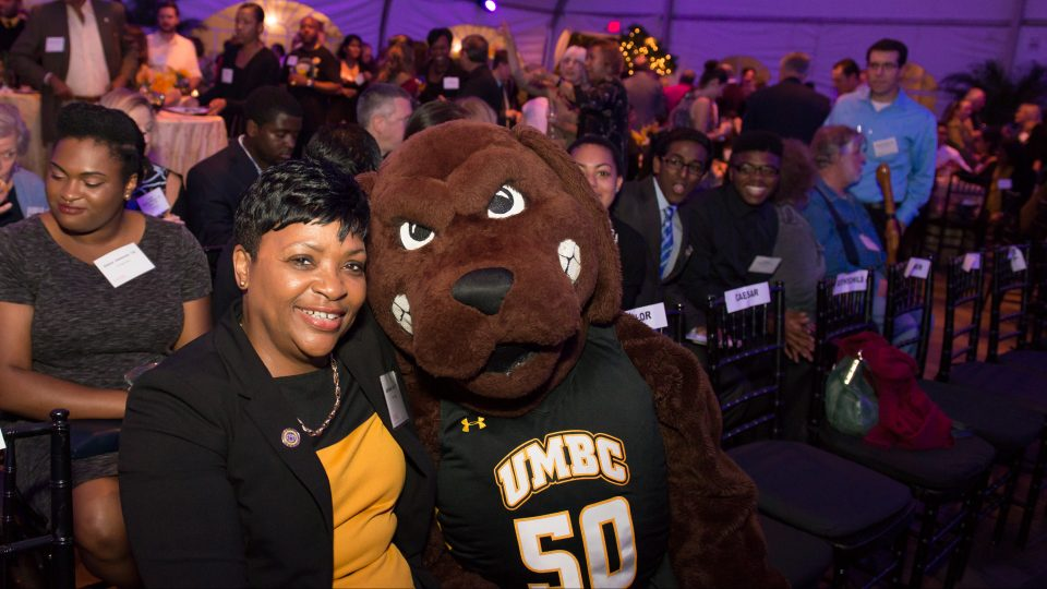 Maryland House Speaker Adrienne Jones, in gold and black, poses with UMBC Retriever mascot, in front of a crowd of people, during an evening celebration.