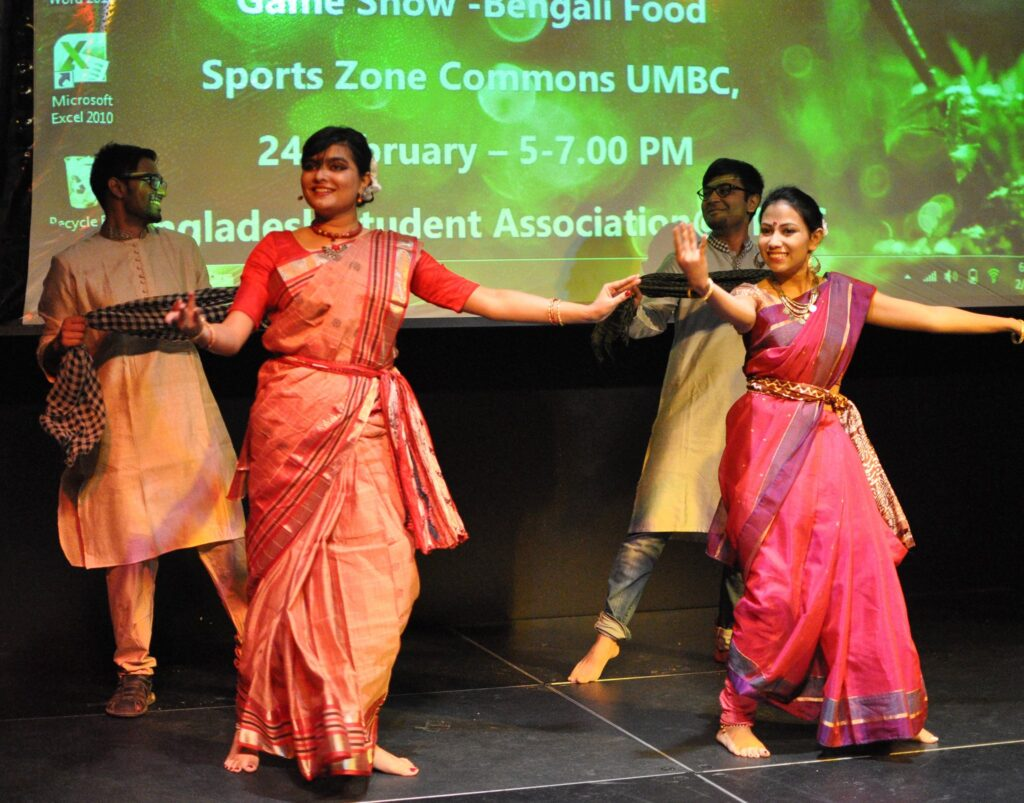 Four dancers demonstrate movements from Bangladeshi cultural traditions, in Bengali clothing.
