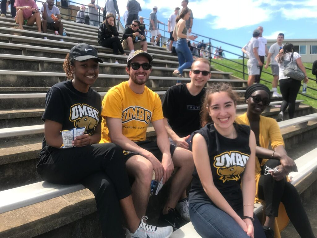Five students wearing UMBC t-shirts sit, smiling, in the stands at an outdoor athletic game.