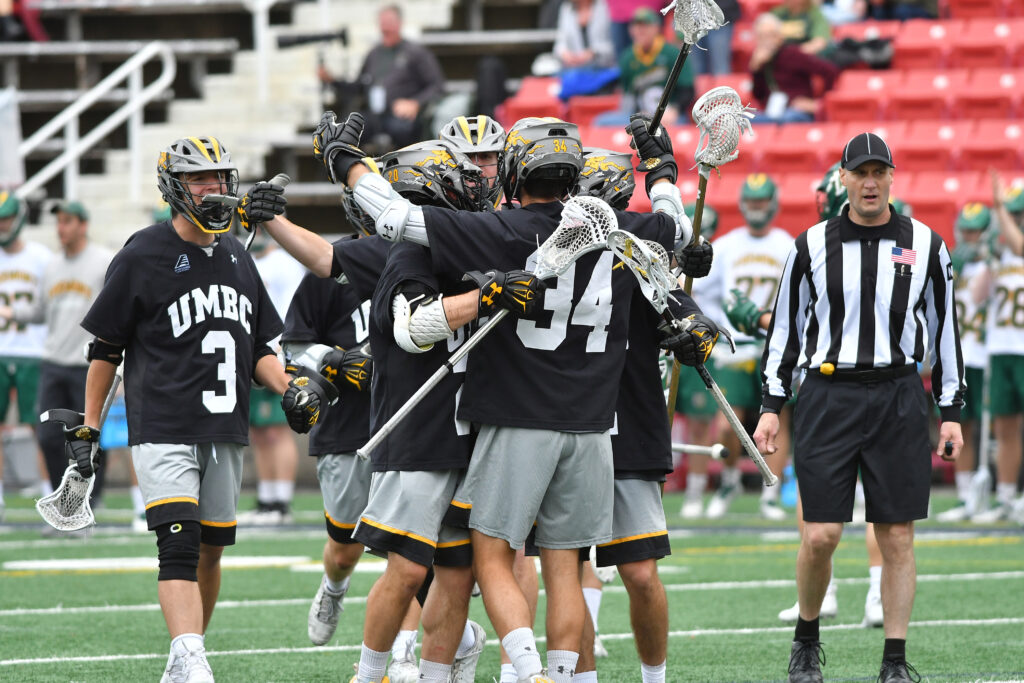 Men's lacrosse players embrace on the field, after a big victory
