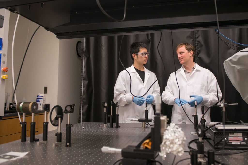 Two scientists in white coats, glasses, and gloves stand in a physics lab.