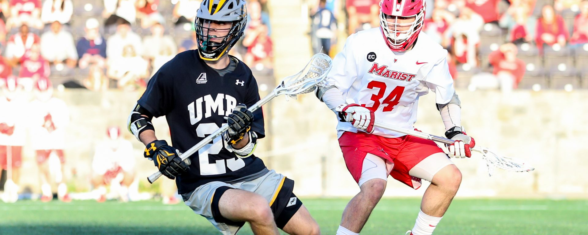 UMBC lacrosse player in black, gold and gray uniform and Marist lacrosse player in red and white uniform, on the field.