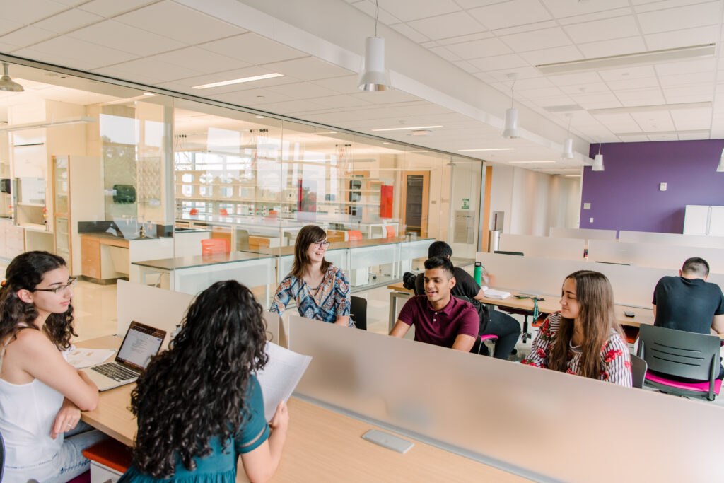 Fives students sit at tables in a shared meeting and work space in a brightly lit new building.