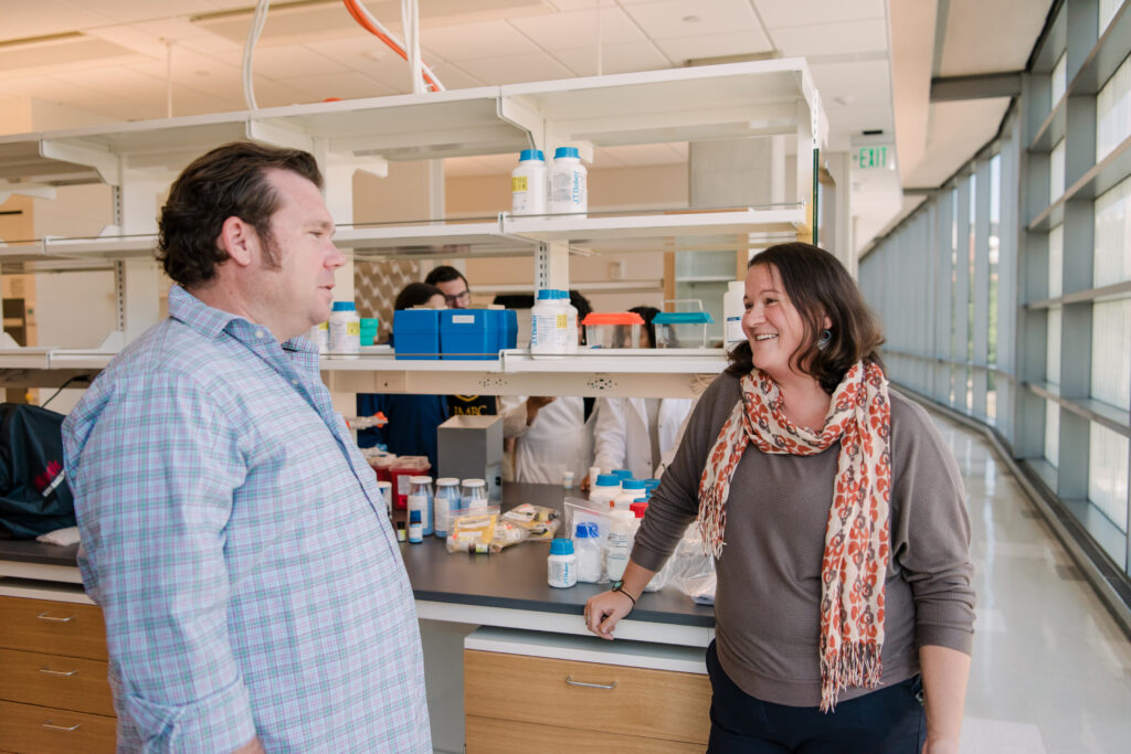 Two researchers in conversation in a lab