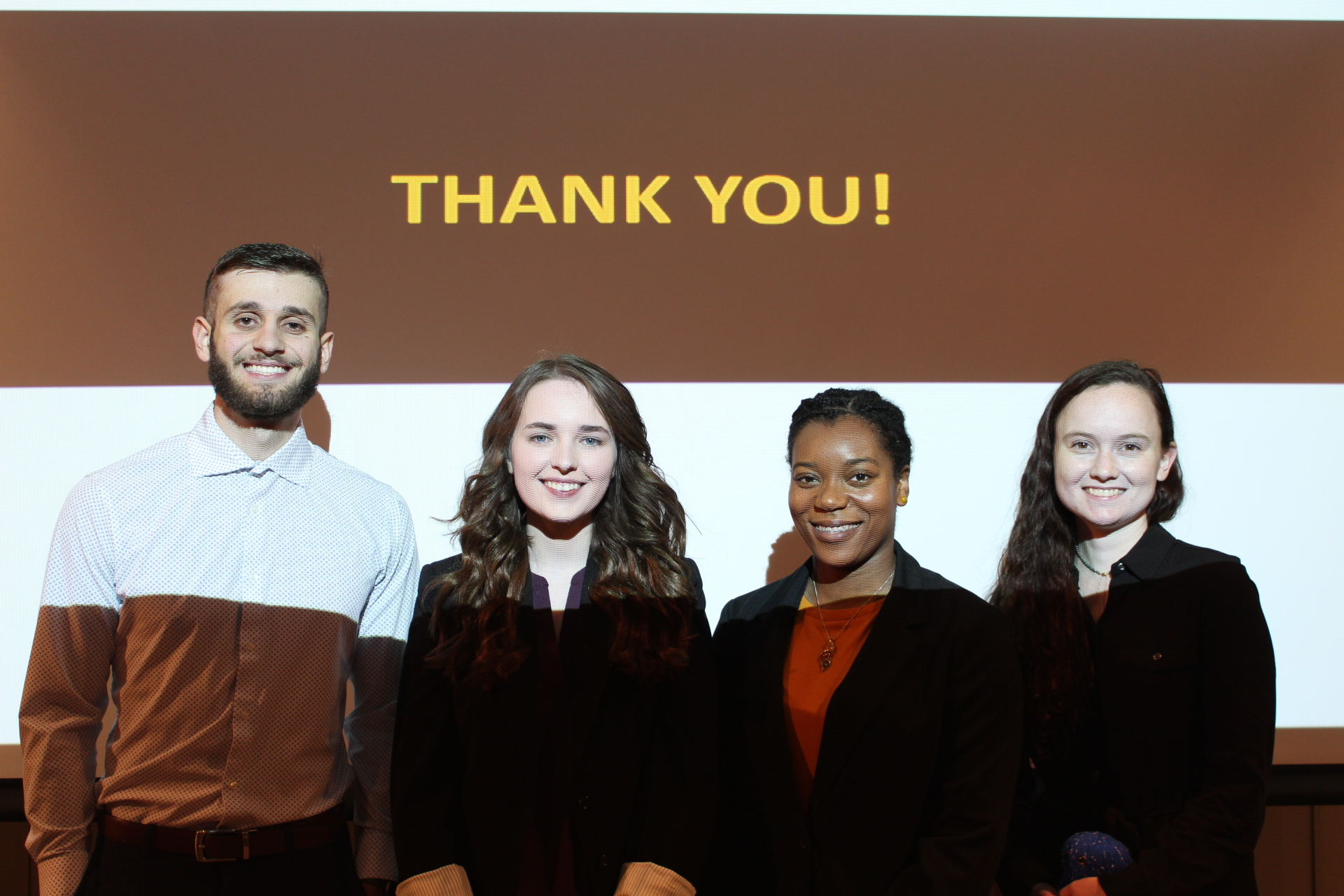 "Four students standing in front of ""thank you"" screen."