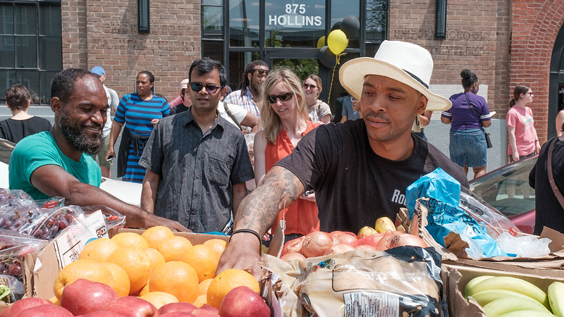 Baltimore city locals buy produce from an Arraber cart.