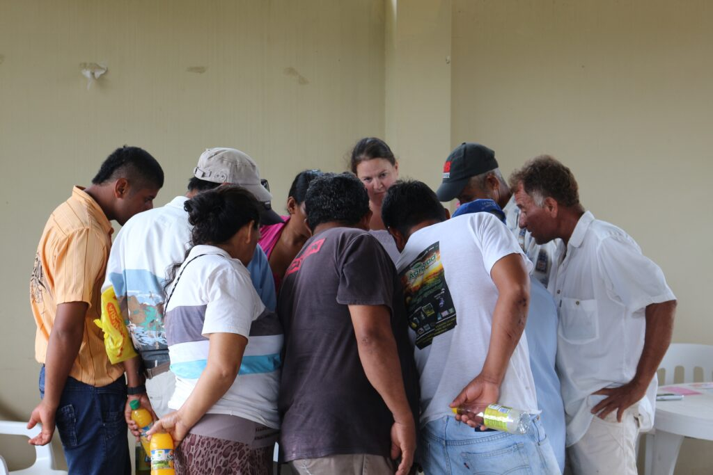 Maggie Holland (center, rear), geography and environmental systems, interviews a group of farmers in the Amazon about the forests on their properties. Photo courtesy Maggie Holland.