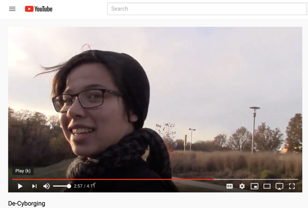 "Screenshot from film ""De-Cyborging,"" featuring a young woman outdoors, wearing a cap, scarf, and glasses."