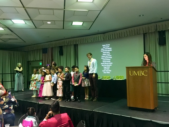 A UMBC male graduate student stands on stage with a mixed group of local elementary school age students for a celebration.
