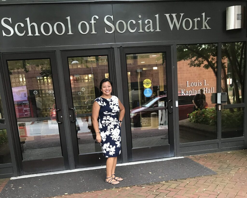 """Woman in black and white floral dress and sandals stands outside a building reading """"School of Social Work,"""" smiling"""