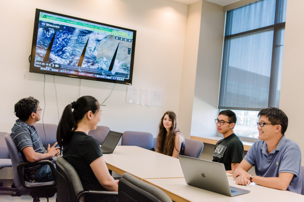 Lab group meets in a conference room with a large screen displaying satellite data on the wall.