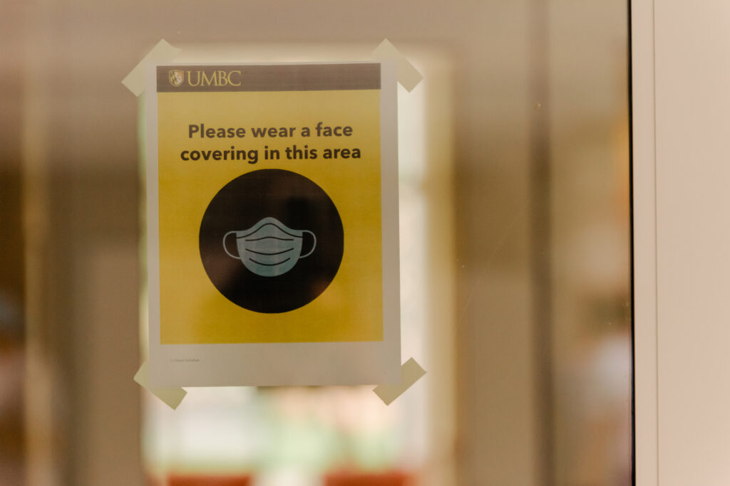 "Sign reads, ""Please wear a face covering in this area."""