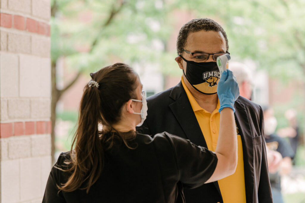 Man in polo shirt and blazer, wearing UMBC face mask, gets temperature taken by medical professional outdoors