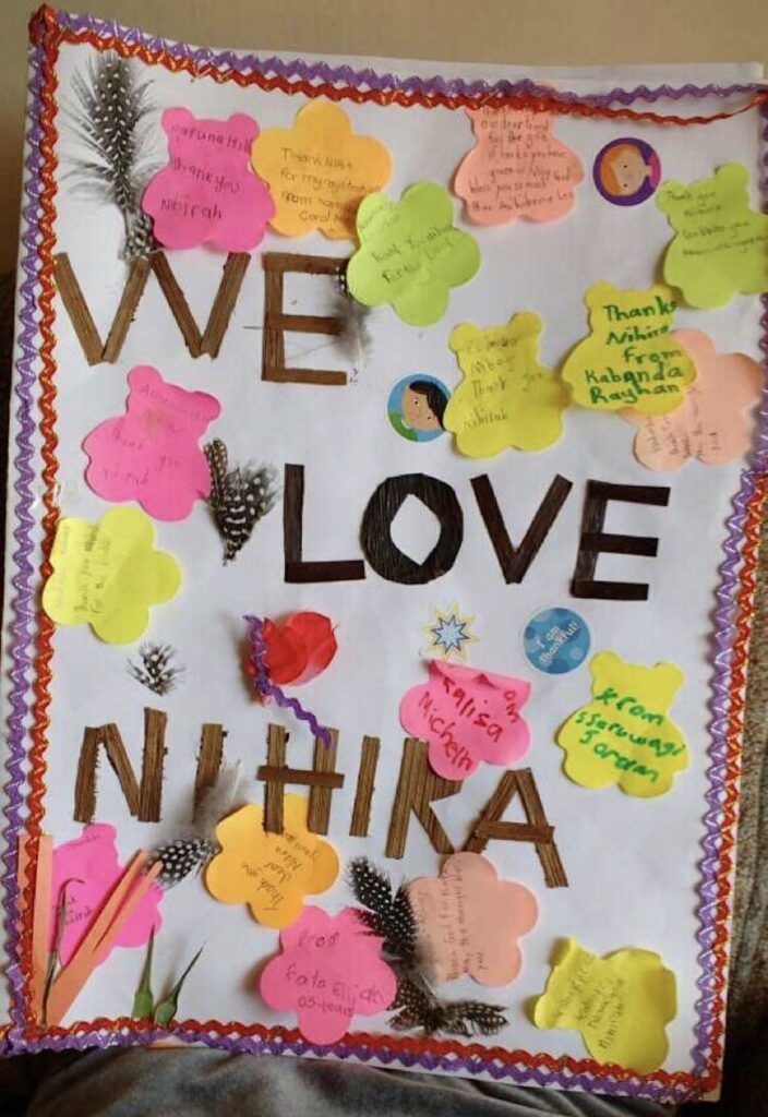 A white paper made into a card is decorated with yellow, pink, and peach bear cut outs with names written inside the cut-outs, purple and orange zigzag strips are pasted on the right and left sides of the paper, with the words We Love Niihira cut out of different colored paper and  pasted in the middle of the card.