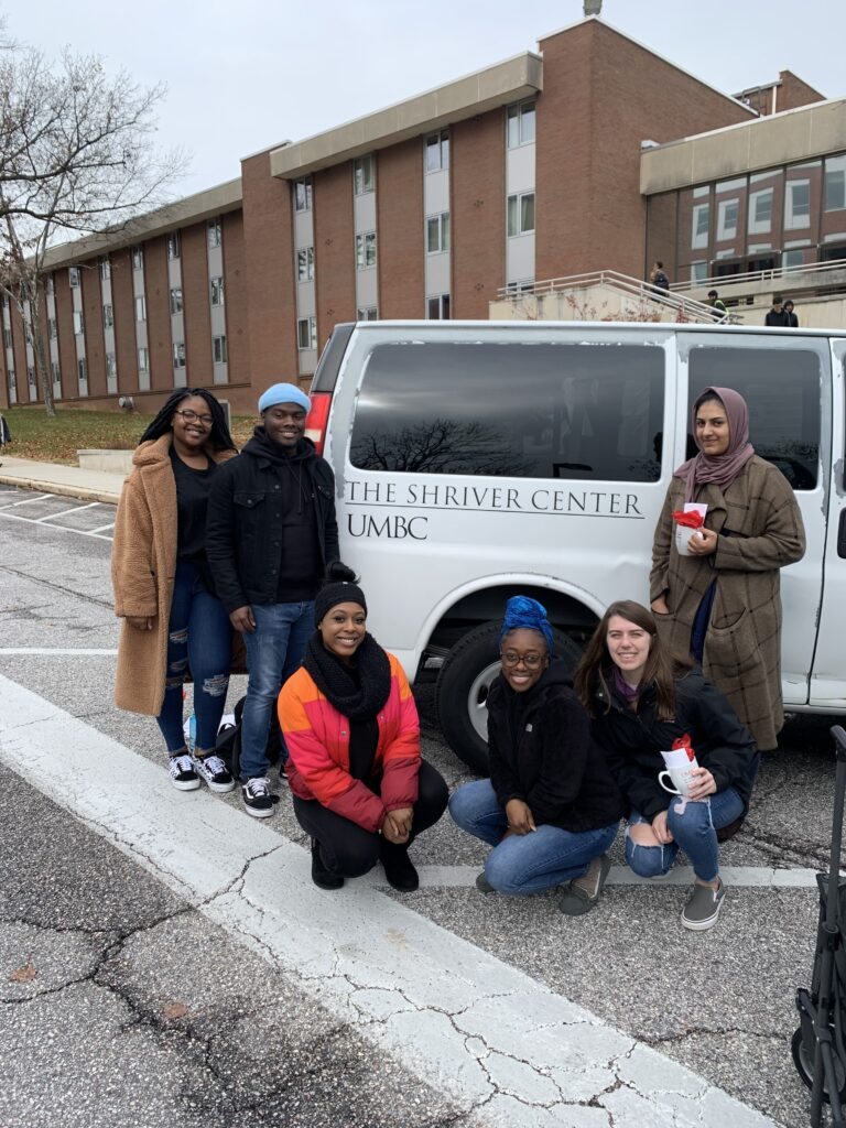 A group of six college students wearing winter jackets, stand in front of a a white van that has lettering that reads The Shriver Center UMBC. Three of them are kneeling on the pavement.