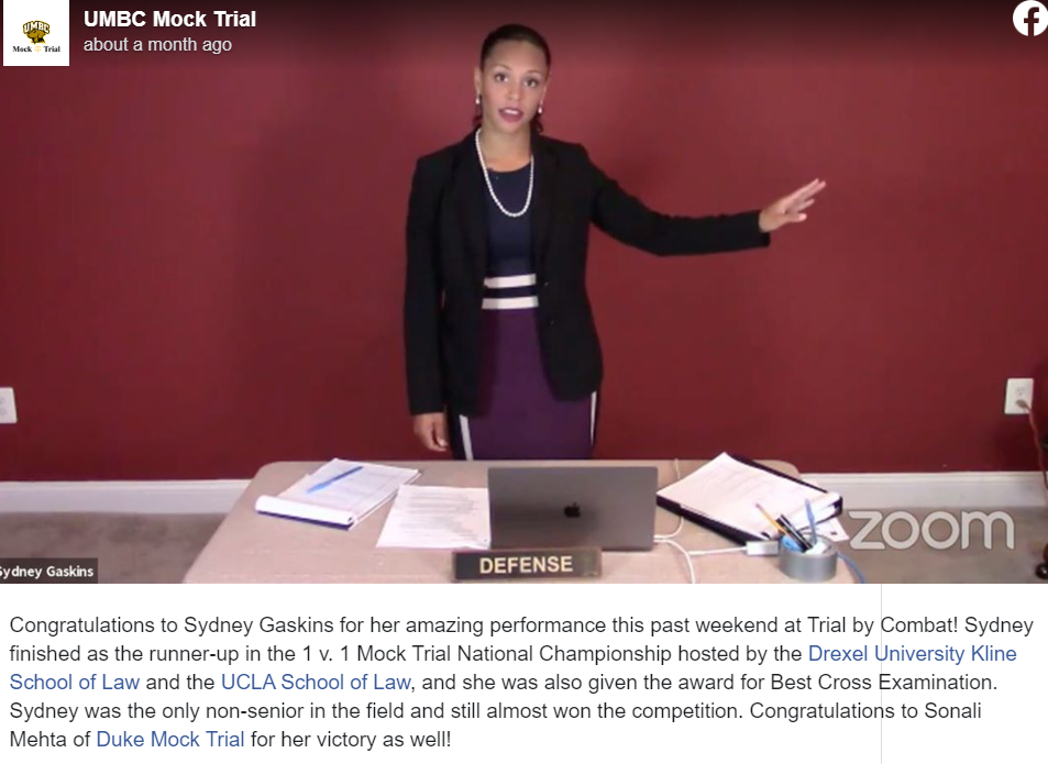 A UMBC Mock Trial Facebook post of a young woman with black hair pulled back wearing a dark purple dress with white stripes on the waist, a black blazer, and pearl  necklace point to her left and stands behind a beige table that has a laptop and papers spread across it.