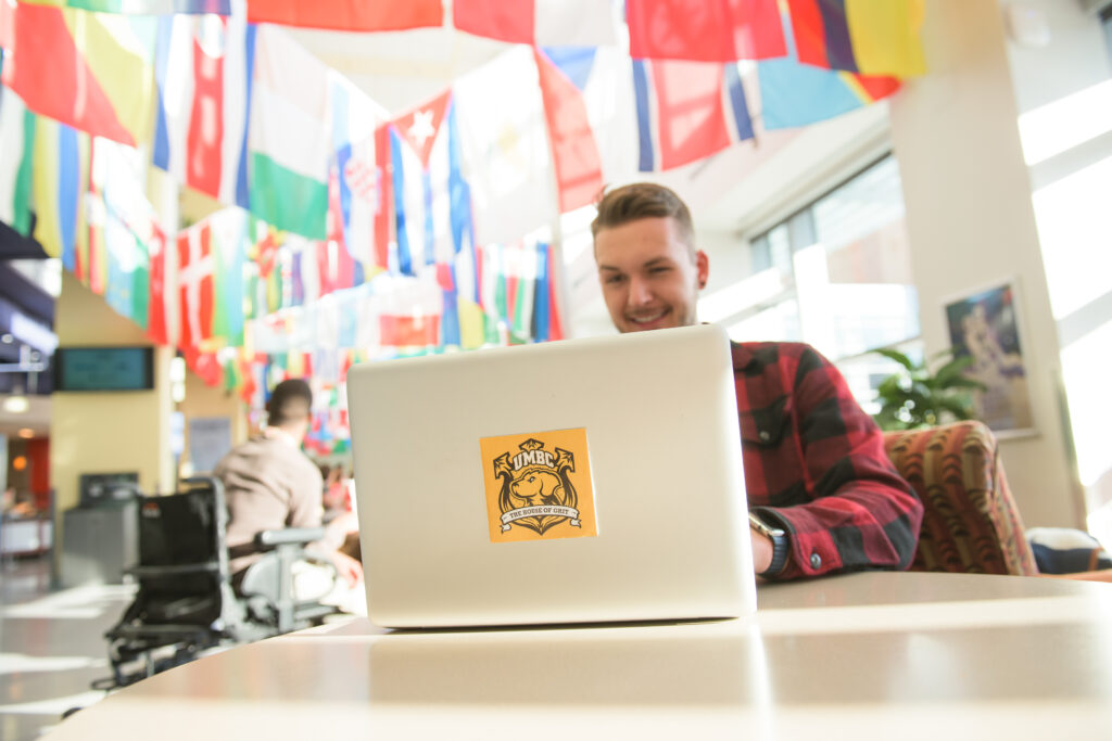 """Man works on computer in a room filled with flags. His laptop has a sticker with a Retriever and """"UMBC"""" on it, reading """"The House of Grit"""""""