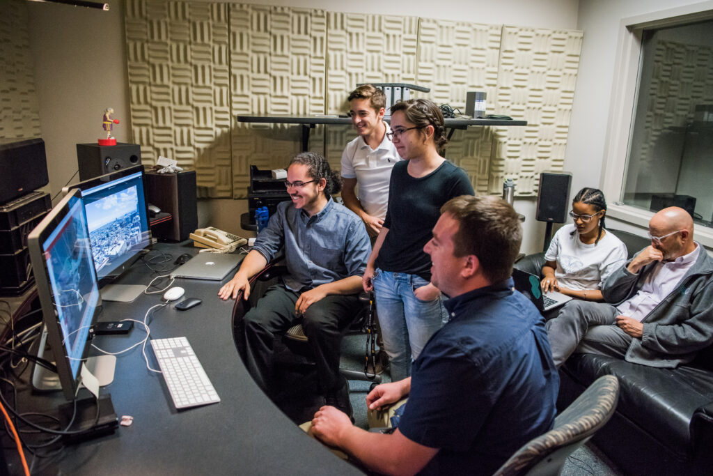Four students gather around monitors, with a professor and student sitting in the background.
