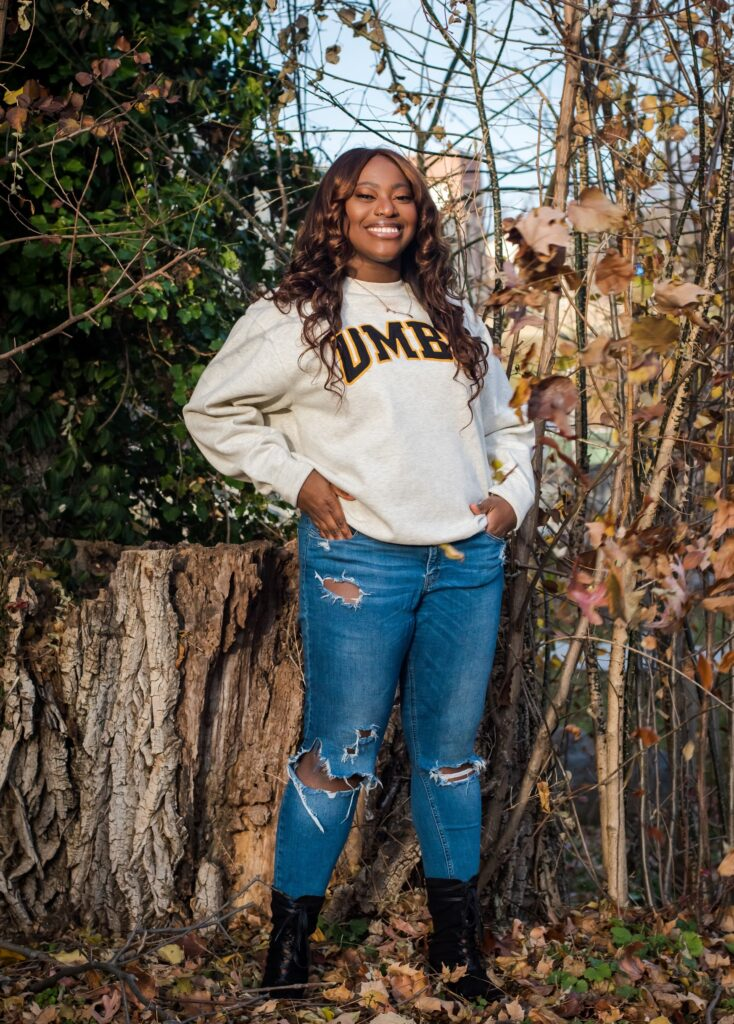 Young woman wearing ripped blue jeans, a white sweatshirt with the words UMBC written in the middle in black, and black boots, stands in front of some trees and shrubs while smiling at camera.